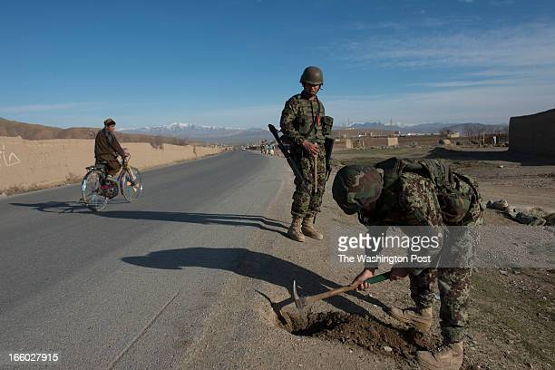 Afghan Army soldiers check for IEDs on Saturday March 30 2013 along the Kabul Paktia Hwy in Logar Province Afghanistan Afghan soldiers use only a...