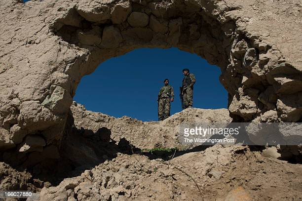 Afghan Army soldiers survey an area where recent kidnappings and Taliban activities have occurred in the Village of Mango Khel on Saturday March 30...