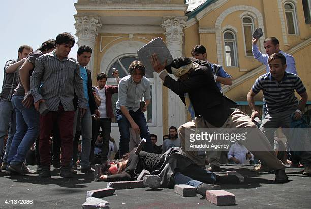 Afghan artists perform a role play to depict the lynching of Afghan woman Farkhunda during a protest demanding justice for a woman who was beaten to...