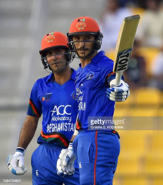 Afghan batsman batsman Rahmat Shah celebrates after scoring a halfcentury as Hashmatullah Shahidi looks on during the one day international Asia Cup...