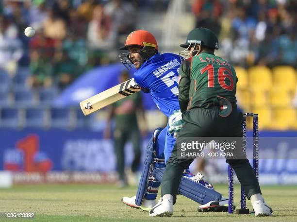 Afghan batsman Hashmatullah Shahidi plays a shot as Bangladesh wicketkeeper Liton Das looks on during the one day international Asia Cup cricket...