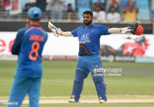 Afghan batsman Mohammad Shahzad celebrates after scoring a century during the one day international Asia Cup cricket match between Afghanistan and...