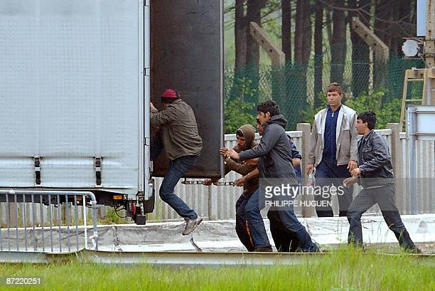 Afghan border escorts help illegal migrants to get into a truck on May 14 2009 in Calais northern France Thousands of migrants pass through Calais...