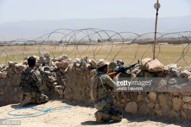 Afghan Border Police personnel keep watch during an ongoing battle between Pakistani and Afghan Border forces near the Durand line at Spin Boldak in...
