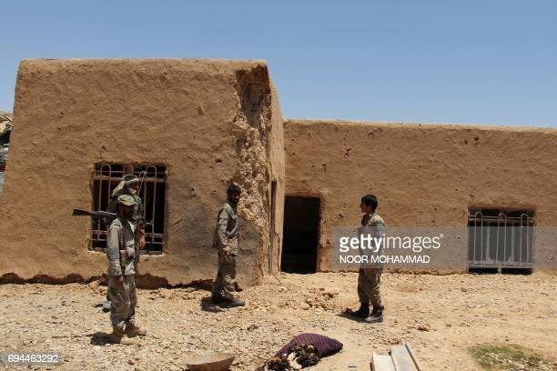 Afghan Border Police personnel walk through an outpost damaged in an airstrike in the Nad Ali district of Helmand province on June 10 2017 An...