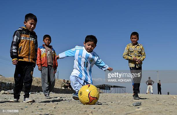 Afghan boy fiveyearold Murtaza Ahmadi a young Lionel Messi fan plays football as he wears a donated and signed shirt by Messi on a field in Kabul on...