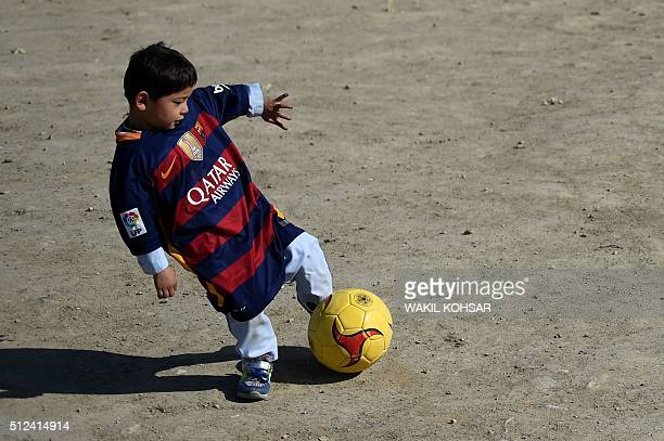 Afghan boy fiveyearold Murtaza Ahmadi a young Lionel Messi fan plays football as he wears a shirt donated and signed by Messi on a field in Kabul on...