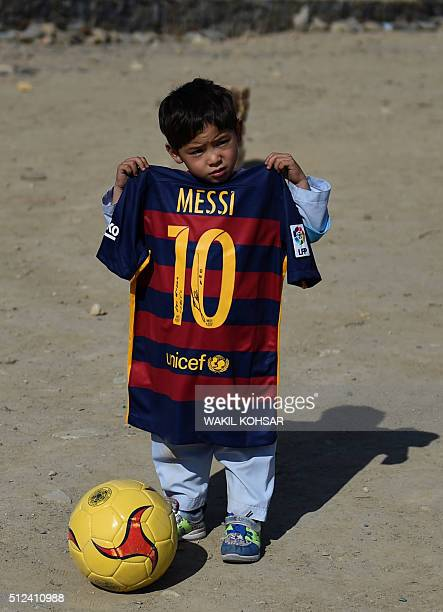 Afghan boy fiveyearold Murtaza Ahmadi a young Lionel Messi fan poses with a shirt donated and signed by Messi on a field in Kabul on February 26 2016...