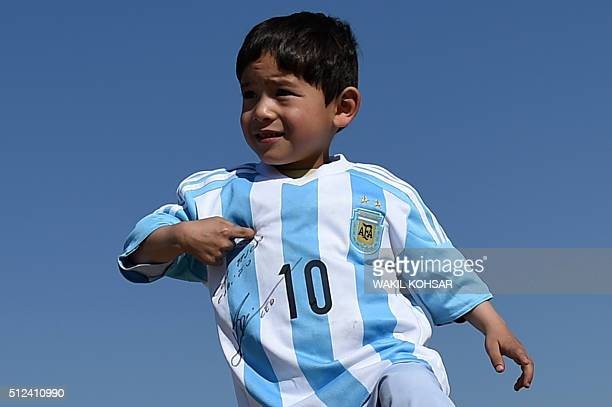 Afghan boy fiveyearold Murtaza Ahmadi a young Lionel Messi fan poses in a shirt donated and signed shirt by Messi on a field in Kabul on February 26...