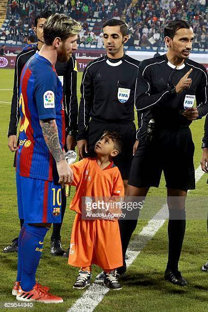 Afghan boy Murtaza Amadi meets with Lionel Messi of Barcelona prior to the friendly soccer match between Al-Ahli Saudi and Barcelona at Al-Gharrafa...