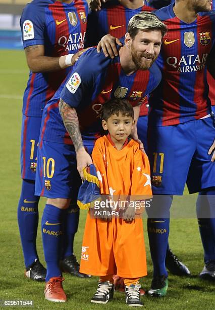 Afghan boy Murtaza Amadi poses with Lionel Messi of Barcelona during the Qatar Airways Cup match between FC Barcelona and Al-Ahli Saudi FC on...
