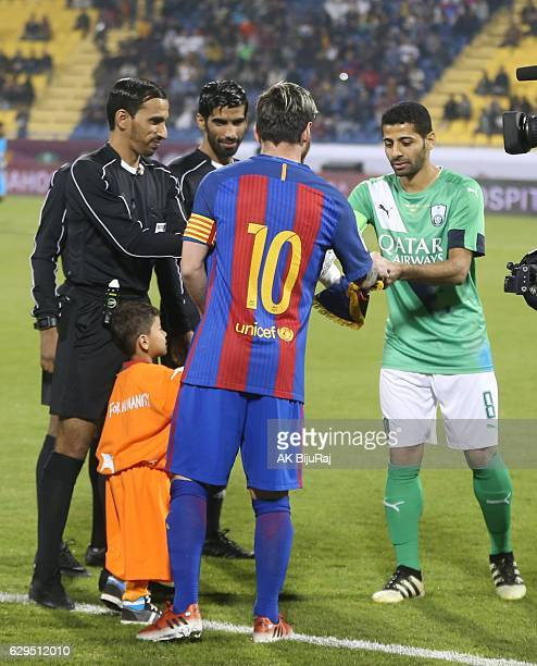 Afghan boy Murtaza Amadi with Lionel Messi of Barcelona during the Qatar Airways Cup match between FC Barcelona and Al-Ahli Saudi FC on December 13,...