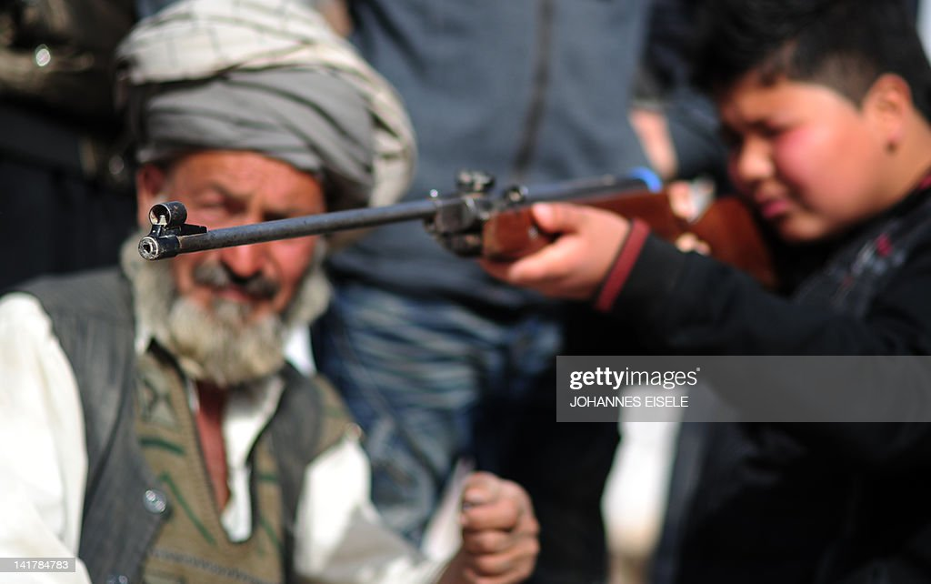 Afghan boy shoots with an airgun next to : News Photo