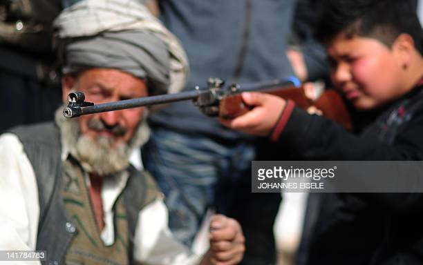 Afghan boy shoots with an airgun next to the traditional Afghan sport Buzkashiin Mazari Sharif on March 23 2012 The ancient game of Buzkashi is an...