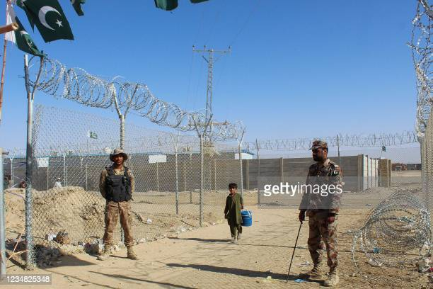 Afghan boy walks by the fences guarded by the Pakistani paramilitary personnel at the Pakistan-Afghanistan border crossing point in Chaman on August...