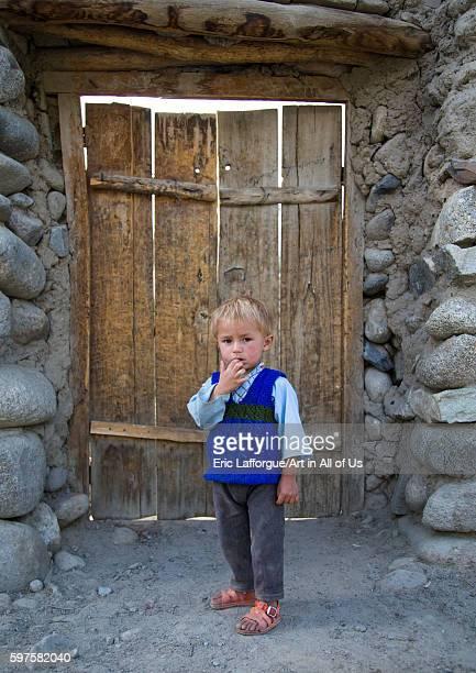Afghan boy with blonde hair in front of a wooden door badakhshan province khandood Afghanistan on August 9 2016 in Khandood Afghanistan