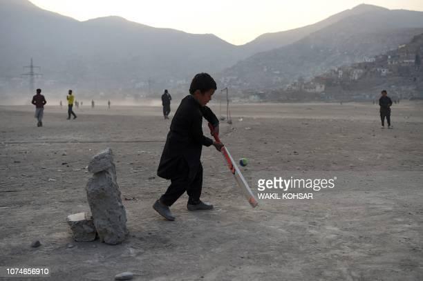 Afghan boys play cricket at an esplanade at Shuhada Lake in Kabul on December 23 2018