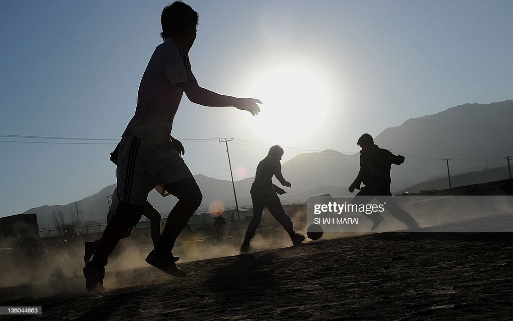 Afghan boys play football in a field in : News Photo