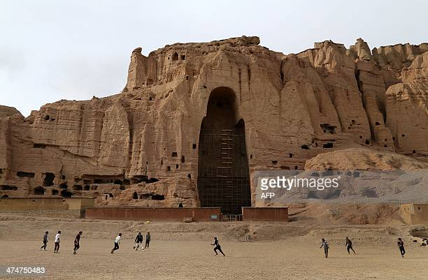 Afghan boys play soccer in front of the empty seat of one of two Buddha statues destroyed by the Taliban in 2001 in Bamiyan province on February 24...