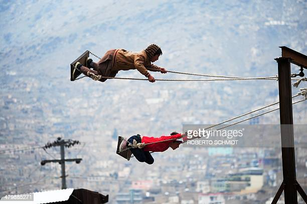 Afghan boys take flight on swings at a fair set up in a field near the Sahki Shrine during Nowruz festivities which marks the Afghan New Year in...