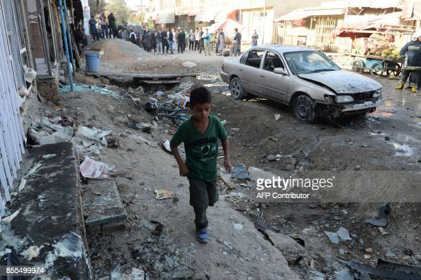Afghan boys walks at the site of a suicide bomb attack near a Shiite mosque in Kabul on September 29 2017 Up to six people were killed when a suicide...