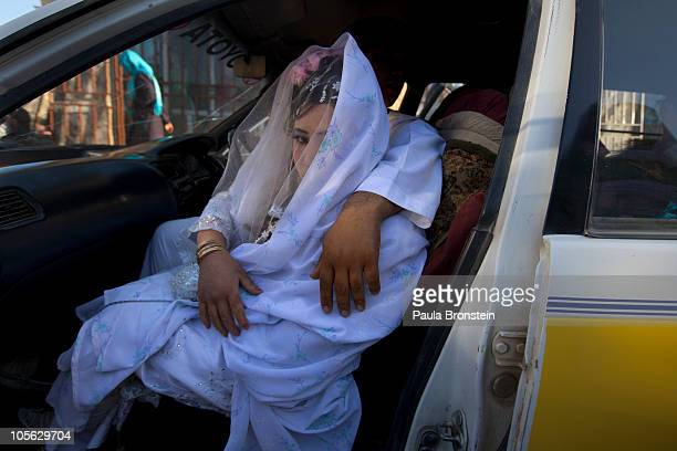 Afghan bride Zahara is held by the grrom Gulam Ali as they leave for the wedding ceremony in a taxi October 14 2010 in Bamiyan Afghanistan At local...