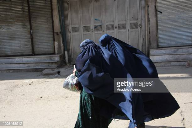 Afghan burqa clad women walk past deserted markets, in Kabul, Afghanistan, 28 March 2020. Kabul, a city with an estimated population of six million,...