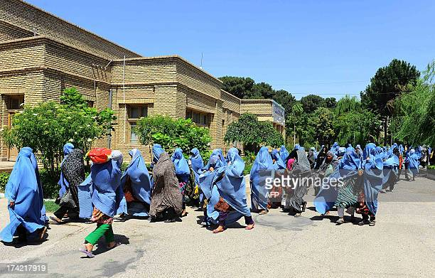 Afghan burqa clad women walk walk down a street with food denotations from a governors office during the month of Ramadan in Herat on July 21 2013...