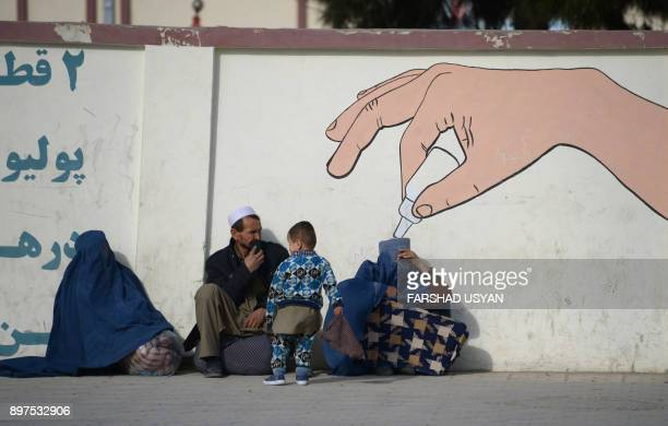 TOPSHOT Afghan burqaclad women along with a man and a child sit together along a roadside in MazariSharif on December 23 2017 / AFP PHOTO / FARSHAD...