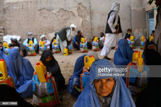 TOPSHOT Afghan burqaclad women receive aid by a charity during the holy month of Ramdan in Herat province on June 7 2018 Muslims throughout the world...