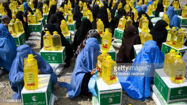 Afghan burqa-clad women sit as they receive aid items by a charity during the holy month of Ramdan in Herat province on May 23, 2019. - Muslims...