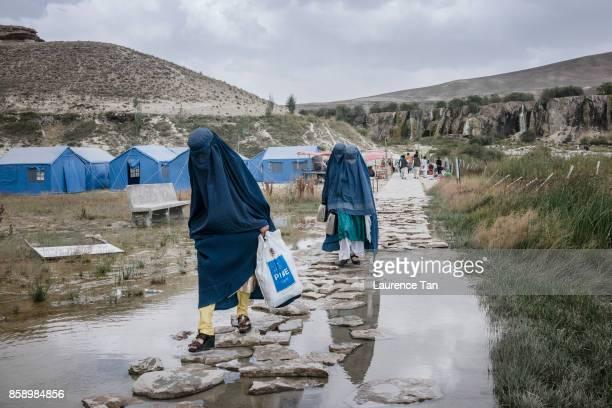 Afghan burqaclad women walk along a path near the Bande Haibat lake at Bande Amir Afghanistan's first national park on August 13 2017 in Bande Amir...