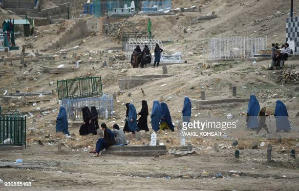 Afghan burqaclad women walks through a cemetery near the old fortress of Bala Hissar in Kabul on March 23 2018 / AFP PHOTO / WAKIL KOHSAR