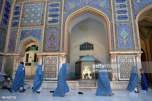 Afghan burqaclad women walks through the courtyard of Jama Mosque during Eid alAdha prayers in Herat on September 1 2017 Afghans have started...