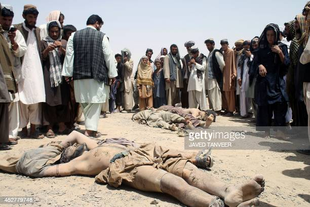 Afghan bystanders look at the bodies of insurgents following an attack by the Taliban in Spin Boldak district of Kandahar province on July 27 2014 A...