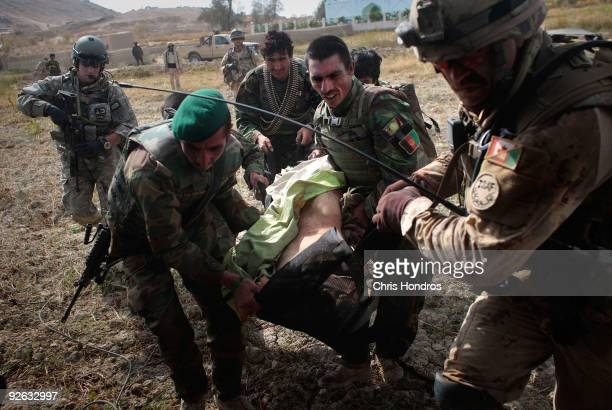 Afghan, Canadian and American troops carry a grievously wounded unidentified Afghan National Army soldier to a waiting Medivac helicopter of the 82nd...