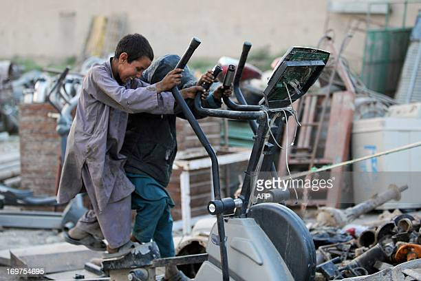 Afghan child labourers play on discarded fitness machines at the Nahre Shahi district of MazariSharif on May 31 2013 Tens of thousands of children in...