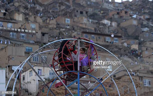 Afghan childen ride on a swing at a fair set up in a field at The Sakhi Shrine in Kabul on March 20 for Nowruz festivities as they mark the Afghan...