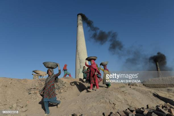 TOPSHOT Afghan children carry coal collected from a brick factory on the outskirts of Kabul on June 1 2018