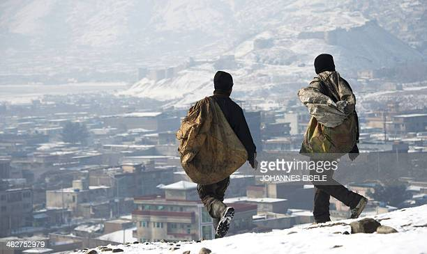 Afghan children carry garbage bags down a hilltop overlooking Kabul on January 9 2014 As winter sets in across Central Asia many Afghans struggle to...