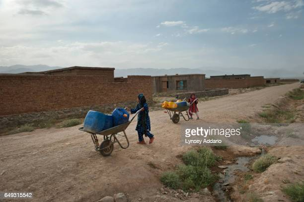 Afghan children do their chores in the mostly abandoned land allocation settlement of AliceGhan about 30 miles outside of Kabul Afghanistan July 22...