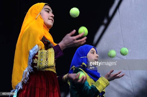 Afghan children from The Mobile Mini Circus for Children juggle during a circus show in Kabul on November 29, 2013. The Mobile Mini Circus for...