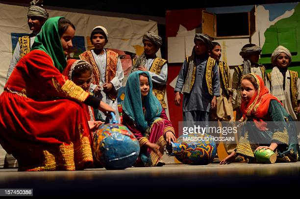 Afghan children from the Mobile Mini Circus for Children perform during a show at the French Culture Center in Kabul on December 3, 2012. Children...