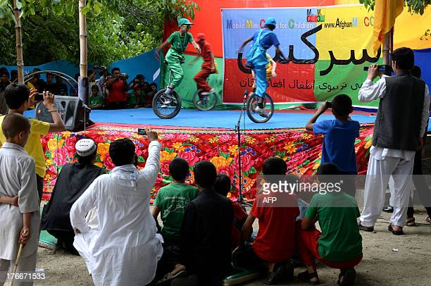 Afghan children from the Mobile Mini Circus for Children perform during a show in Paghman district on the outskirts of Kabul on August 16, 2013....