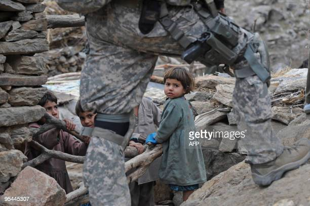 Afghan children look on as a US soldier from the Provincial Reconstruction team Steel Warriors patrols in the mountains of Nuristan Province on...
