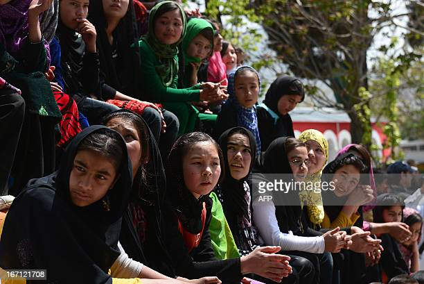 """Afghan children look on as others from The Mobile Mini Circus for Children take part in a performance to honour """"World Circus Day"""" at their Centre in..."""