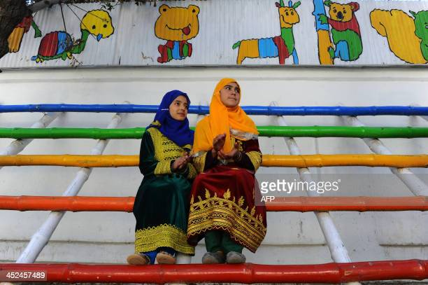 Afghan children look on as performers from The Mobile Mini Circus for Children take part in a circus show in Kabul on November 29, 2013. The Mobile...