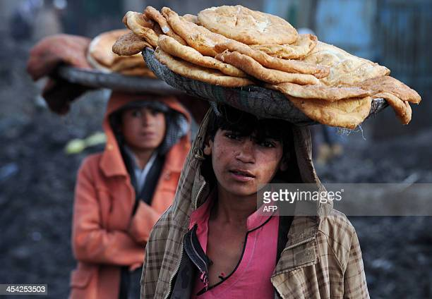 Afghan children look on as they wait for customers while selling food on a street in Kabul on December 8 2013 The UN mission in Afghanistan...
