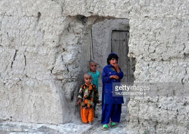Afghan children look on as unseen US soldiers from Bravo Troop 171 CAV Forward Operating Base Wallakan patrol in the village of Rambasi Dand District...