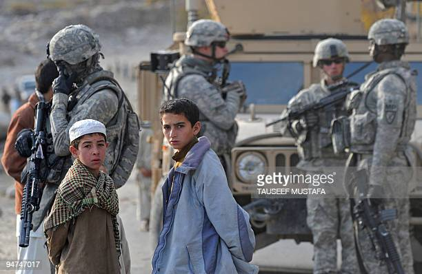 Afghan children look on as US soldiers from 277 Field Artillery MPs 359th Steel Warriors patrol in Nuristan Province on December 18 2009 US President...